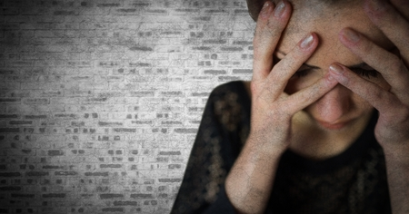 restless: Digital composite of Woman hands over face against white brick wall with grunge overlay