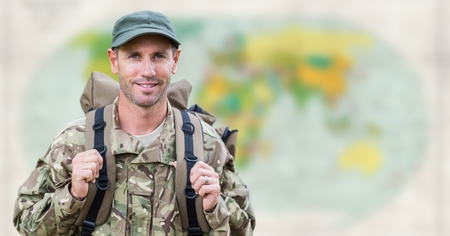 Digital composite of Soldier with backpack against blurry map Stock Photo