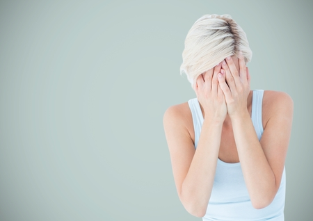 Digital composite of Woman crying into hands against light blue background