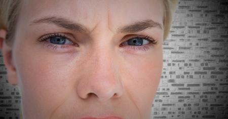 Composite numérique de Gros plan des yeux en colère de la femme contre le mur de briques blanches Banque d'images - 79222382
