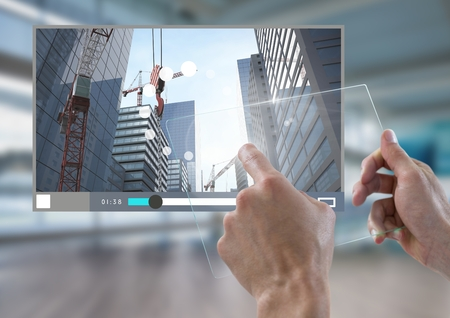 Digital composite of Hand touching glass tablet City Video Player Architecture App Interface