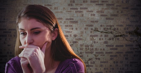woman looking down: Digital composite of Woman thinking against brown brick wall