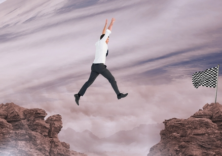 Digital composite of businessman jumping with his hands up to catch the checker flag
