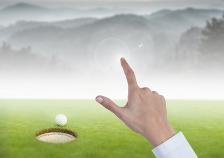 Digital composite of Womans Hand touching golf course mountains