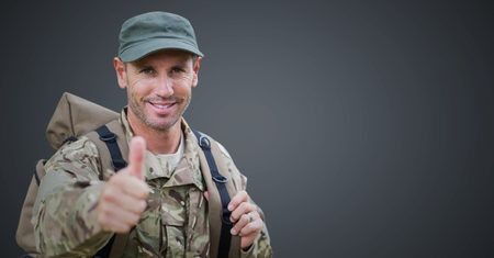 Digital composite of Soldier thumbs up against grey background Stock Photo
