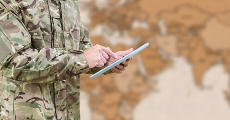Digital composite of Soldier mid section with tablet against blurry brown map