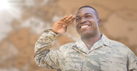 Digital composite of Soldier smiling and saluting against blurry brown map with flare