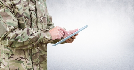 Digital composite of Soldier mid section with tablet against white wall