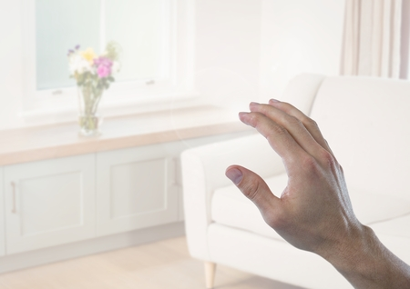 futuristic interior: Digital composite of Hand touching  air of sitting room Stock Photo