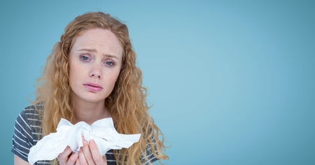 Digital composite of Woman with tissues against blue background Stock Photo
