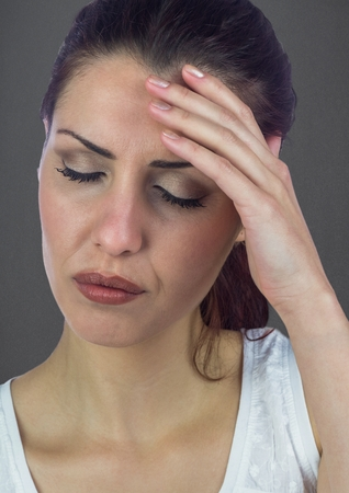 Digital composite of Stressed woman against grey wall