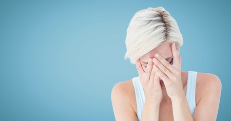 Digital composite of Woman crying in hands against blue background