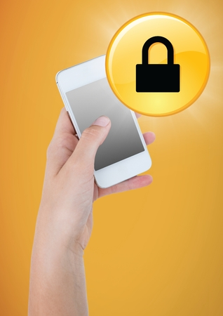 Digital composite of Hand with phone and yellow lock graphic with flare against yellow background Stock Photo