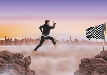 Digital composite of Businessman jumping in the rocks to catch the checker flag Stock Photo