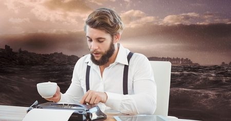 Digital composite of Male hipster using typewriter while holding coffee cup against sea