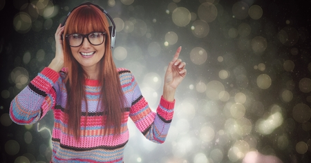 Digital composite of Happy female hipster listening to music over bokeh Stock Photo