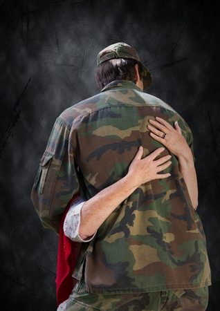 universal love: Digital composite of Back of soldier being hugged against black grunge background