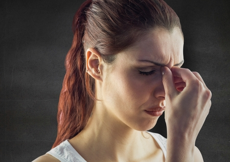 uneasy: Digital composite of Close up of stressed woman against grey wall Stock Photo