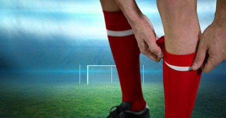 using tablet: Digital composite of Close-up of soccer player adjusting sock on field