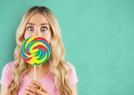 Digital composite of Surprised woman with lollipop candy over green background