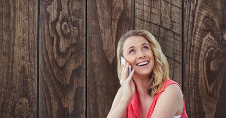 using smart phone: Digital composite of Happy woman using smart phone against wooden wall