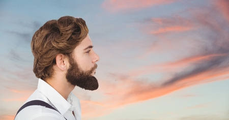 met: Digital composite of Side view of male hipster looking away against cloudy sky
