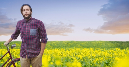 Digital composite of Male hipster with bicycle on flowering field