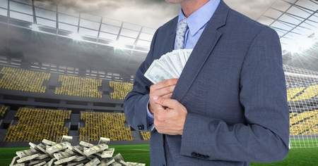 Digital composite of Midsection of businessman hiding money at soccer stadium representing corruption concept