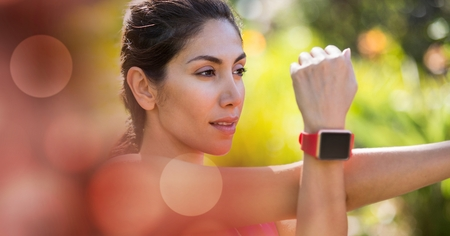 Digital composite of Young woman wearing smart watch while exercising Stock Photo