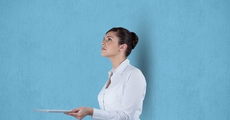 using tablet: Digital composite of Businesswoman holding digital tablet over blue background