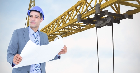 computer animation: Digital composite of Male architect holding blueprint against crane