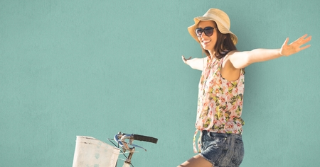 Digital composite of Young woman with arms outstretched riding bicycle Stock Photo