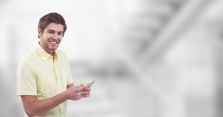 Digital composite of Smiling man holding mobile phone over blur background Stock Photo