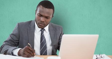 using smartphone: Digital composite of Businessman writing at desk over green background