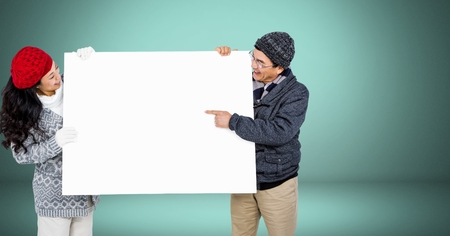 Digital composite of Couple holding blank billboard against green background
