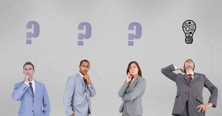 Digital composite of Business people with question marks and light bulb signs on wall Stock Photo