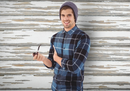 man holding transparent: Digital composite of Smiling hipster holding smoking pipe over wooden wall Stock Photo