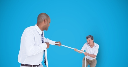 Digital composite of Business people playing tug of war over blue background