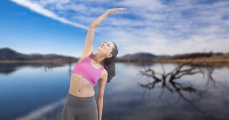 Digital composite of Double exposure of woman performing yoga at lakeshore