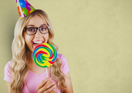luscious: Digital composite of Happy woman wearing party hat while having lollipop