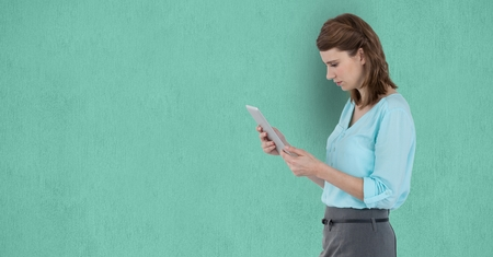 Digital composite of Side view of businesswoman using tablet computer over green background Stock Photo