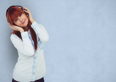 using tablet: Digital composite of Redhead woman wearing headphones over blue background Stock Photo