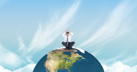 Digital composite of Businessman meditating on earth against sky Stock Photo
