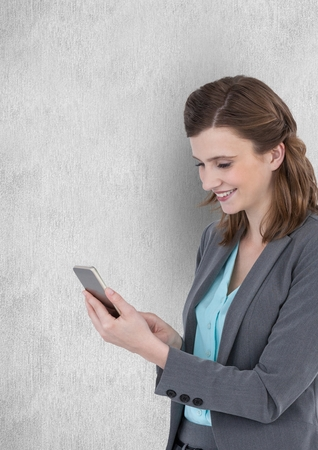 Digital composite of Smiling businesswoman texting on smart phone against wall