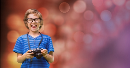 Digital composite of Little boy holding camera while laughing
