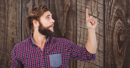 Digital composite of Male hipster pointing upwards against wooden wall