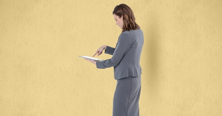 Digital composite of Businesswoman touching screen of tablet PC over beige background