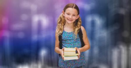 Digital composite of Happy schoolgirl holding books over blur background