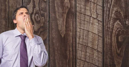covering eyes: Digital composite of Tired businessman yawning against wooden wall
