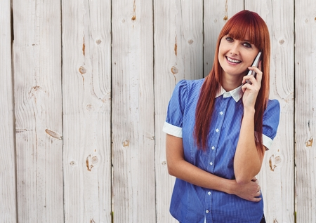 Digital composite of Redhead woman using smart phone over wooden wall Stock Photo